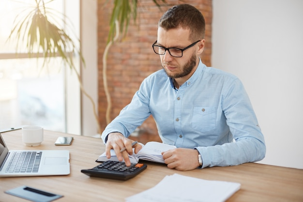 Adult serious bearded caucasian finance manager in glasses and blue shirt sitting in light comfortable company office