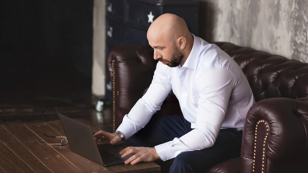 Adult serious man working at the computer in the office