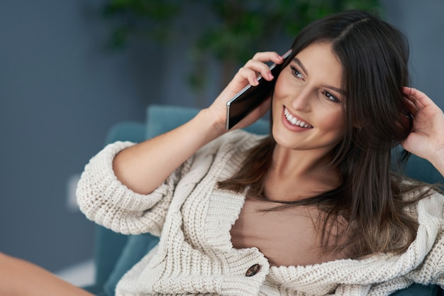 自宅でリラックスしてスマートフォンを使用して大人のセクシーな女性