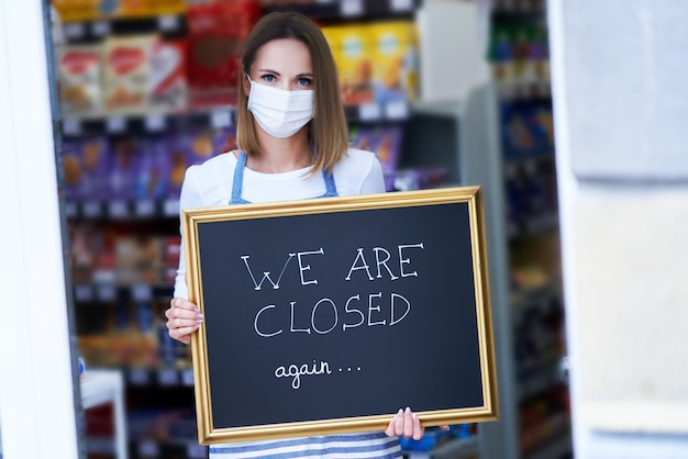 Adult shop assistant holding announcement board