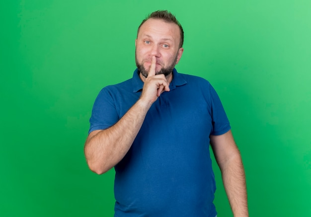 Adult slavic man  and doing silence gesture isolated on green wall with copy space