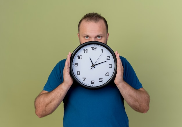 Adult slavic man holding clock looking from behind clock