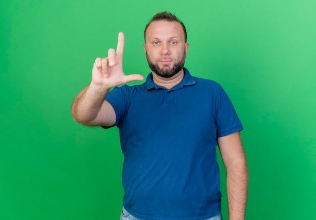 Взрослый славянский мужчина смотрит, делая жест неудачника, изолированного на зеленой стене