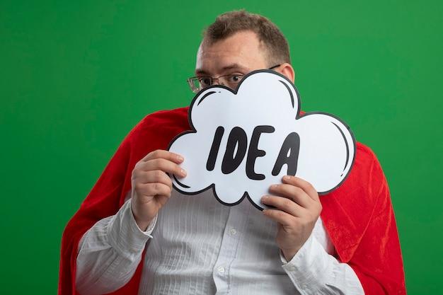 Взрослый славянский супергерой в красном плаще в очках держит пузырь идеи перед лицом сзади, изолированным на зеленой стене