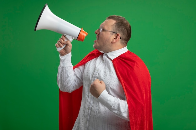 Adult slavic superhero man in red cape wearing glasses standing in profile view talking by speaker clenching fist isolated on green wall with copy space