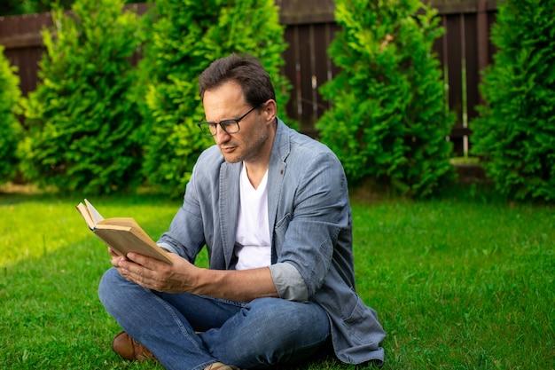 Взрослый умный человек расслабляющий в природе, читая книгу, мужчина-бизнесмен сидит на открытом воздухе в парке с бумажной книгой, отдыхая время отдыха. лето, досуг, самообразование, учеба, концепция хобби. копировать текстовое пространство