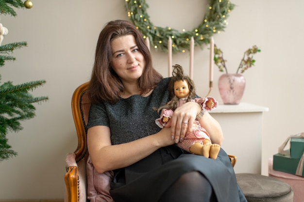 Adult smiling woman sitting in chair with a doll in room with cristmas tree and new year decorationsю