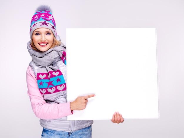 La donna sorridente adulta in abbigliamento esterno caldo tiene il cartello bianco nelle mani e indica su di esso