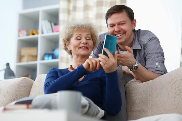 Взрослый сын учит маму пользоваться мобильным телефоном