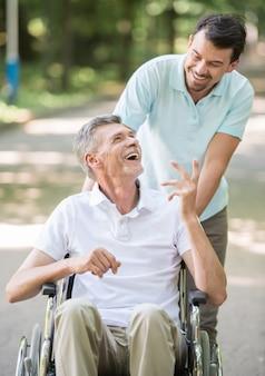 屋外の車椅子で障害のある父親と一緒に歩いている大人の息子