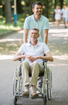 Adult son walking with disabled father in wheelchair outdoor