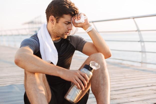 サーモスマグとマットの上に座って、朝の海辺の木製の桟橋でのトレーニングの後、額から汗を拭くトラックスーツの大人のスポーツマン