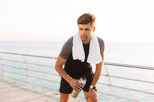 Adult sportsman in tracksuit with towel on neck drinking water from thermos mug, after workout on wooden pier at seaside in morning