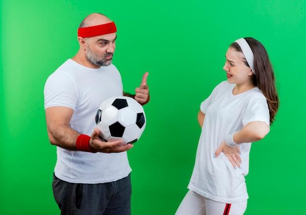 ヘッドバンドとリストバンドを身に着けている大人のスポーティなカップルは、緑の壁で隔離されたお互いを見て腰に手を置いてサッカーボールを持って指さしている自信を持っている男性