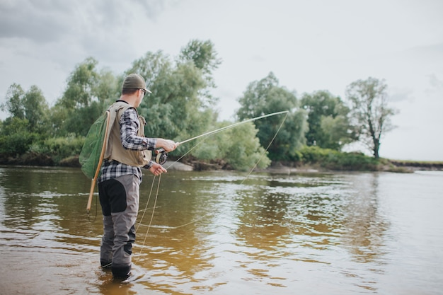 大人は浅く立ってフライロッドを手に持っています。彼は釣りをしています。ガイは片方の手でフライロッドを持ち、もう片方の手でスプーンの一部を持っています。また、男は背中に漁網を持っています。