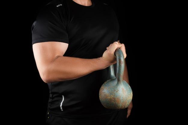 彼の両腕に鉄ケトルベルを保持している黒い服を着た大人の強い運動選手