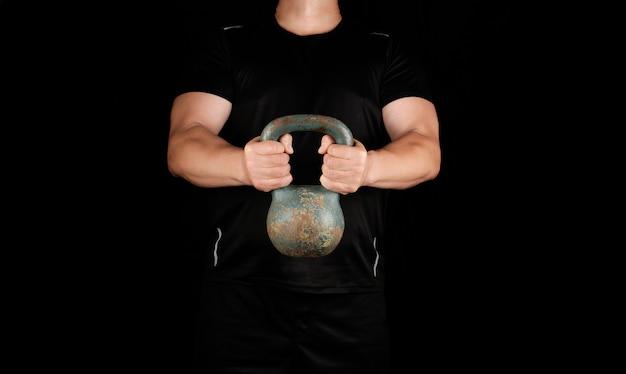 鉄のケトルベルを保持している黒い服を着た大人の強い選手