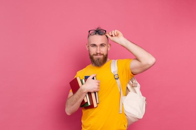 Взрослый студент веселый парень повседневной одежды с бородой и рюкзаком держит книги, изолированные на розовом