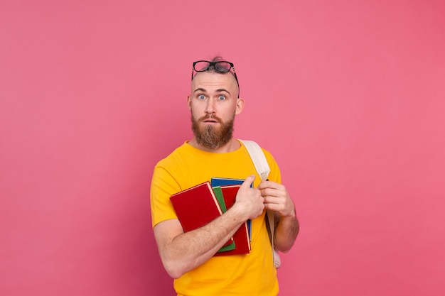 Adult student cheerful casual wear guy with beard and backpack holding books isolated on pink