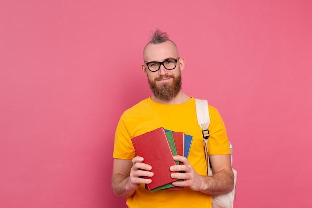 Ragazzo allegro di abbigliamento casual dell'allievo adulto con la barba e lo zaino che tengono i libri isolati sul colore rosa