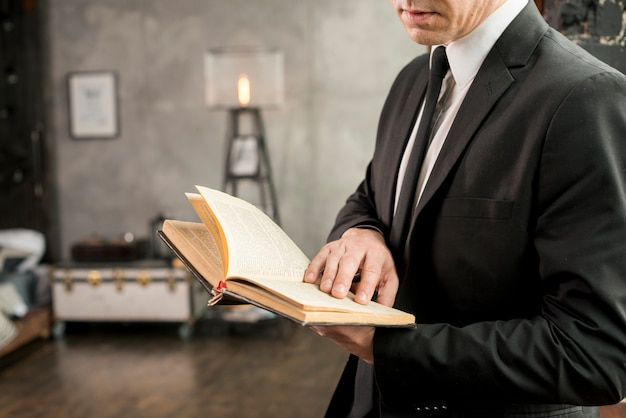 Adult stylish businessman reading book