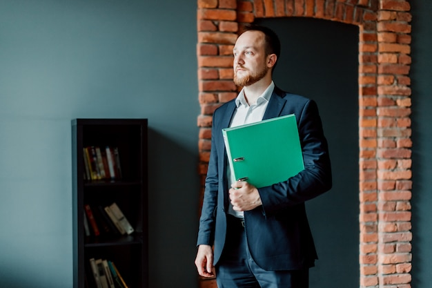 An adult and successful accountant in a suit is standing and holding a green folder in his hands.