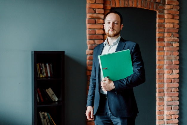 An adult and successful accountant in a suit is standing and holding a green folder