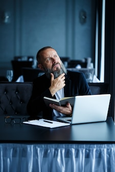 Взрослый успешный бизнесмен мужского пола работает над новым проектом и смотрит на графики роста в блокноте. сидит за столом и работает. смотрит в блокнот и улыбается