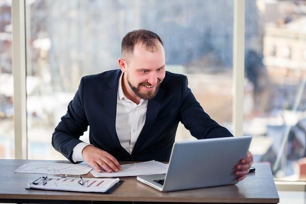 Взрослый успешный бизнесмен-мужчина, учитель, наставник работает над новым проектом. сидит за столом у большого окна. работает на ноуте