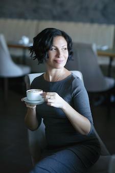 カフェのテーブルに座ってコーヒーを飲む大人の成功した女性