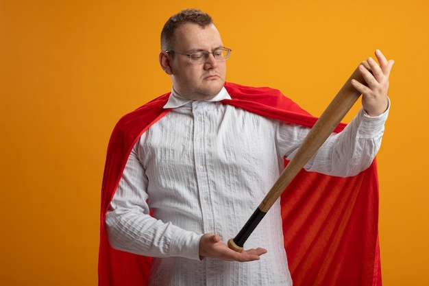 Взрослый супергерой в красном плаще в очках держит и смотрит на бейсбольную биту, изолированную на оранжевой стене