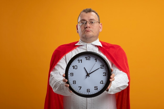 Adult superhero man in red cape wearing glasses looking at front stretching out clock towards front isolated on orange wall