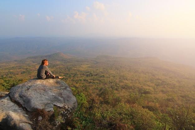 Взрослый турист в черных брюках, куртке и темной шапке сидит на краю скалы и смотрит на туманную холмистую долину