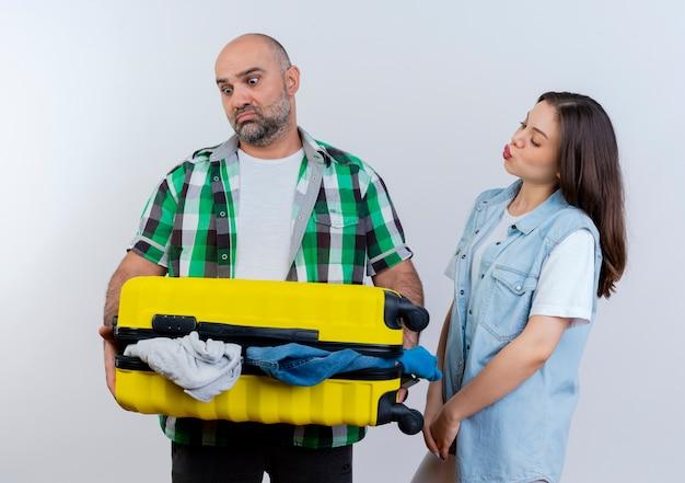 Uomo triste delle coppie del viaggiatore adulto che tiene e che esamina la donna premurosa della valigia che sta nella vista di profilo che tiene le mani insieme guardando la valigia
