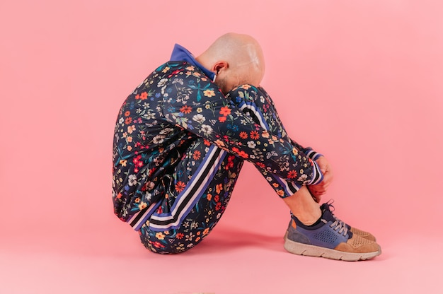 Adult unhappy sad bald depressed man in fashionable trendy tracksuit