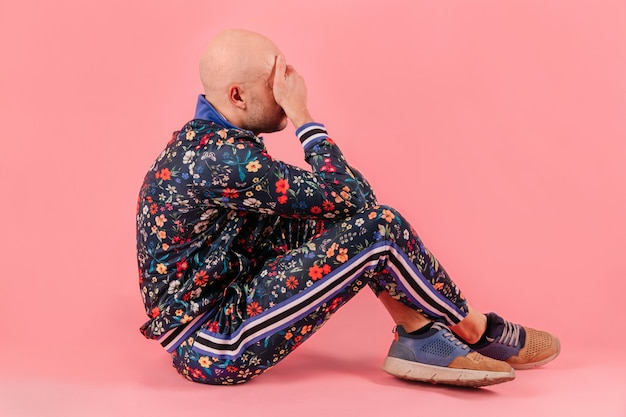 Adult unhappy sad bald  man in fashionable trendy tracksuit isolated on pink wall.  conceptual psychological portrait of stylish despaired boy sitting on ground indoor. odd crying boy.