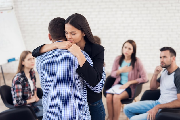 Adult upset woman embraces man during group therapy session.
