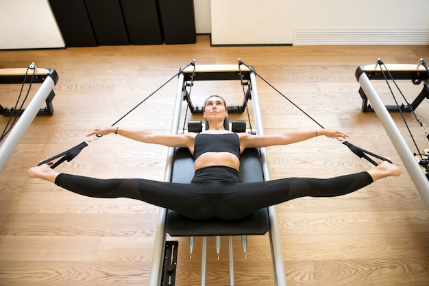 Adult using pilates machine to stretch legs