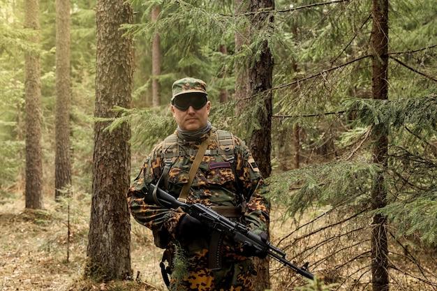 숲에서 무기, 에어소프트 또는 스트라이크볼이 있는 성인 전쟁 팀 게임. 안경, 손에 무기와 군사 위장 유니폼에 육군 군인. 자동 총으로 삼림 지대 제복을 입은 중년 군인 프리미엄 사진
