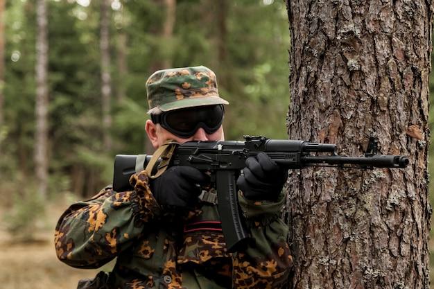 숲에서 무기, 에어소프트 또는 스트라이크볼이 있는 성인 전쟁 팀 게임. 안경, 손에 무기와 군사 위장 유니폼에 육군 군인. 자동 총으로 삼림 지대 제복을 입은 중년 군인