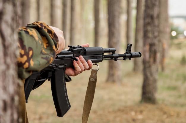 숲에서 무기, 에어소프트 또는 스트라이크볼을 사용한 성인 전쟁 팀 게임. 안경, 손에 무기와 군사 위장 유니폼에 육군 군인. 자동 총으로 삼림 지대 제복을 입은 중년 군인