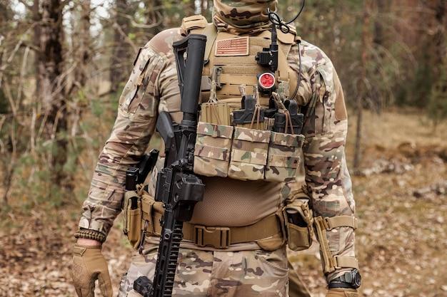 숲에서 무기, 에어소프트 또는 스트라이크볼을 사용한 성인 전쟁 팀 게임. 전투복을 입은 미 육군 레인저스 police us marshal 무기를 들고 있습니다. 총을 든 삼림 지대 군복을 입은 미국 군인