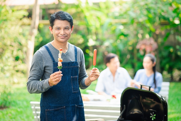 Adult with barbrcue grilled in hand having party with friends