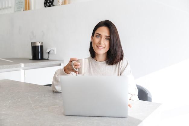 Взрослая женщина 30 лет работает на ноутбуке, сидя на белой стене в светлой комнате