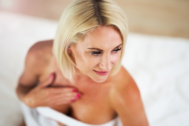 Adult woman applying body moisturizer at home