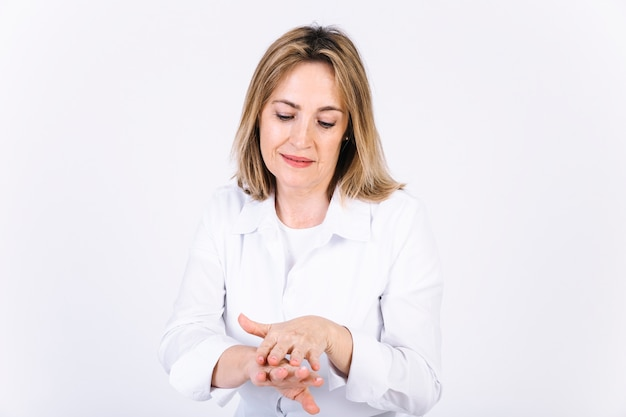 Adult woman applying cream on hands