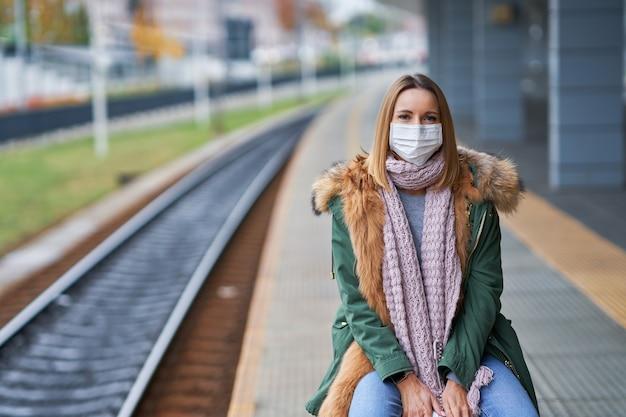 Covid-19 제한으로 인해 마스크를 쓰고 기차역에서 성인 여성