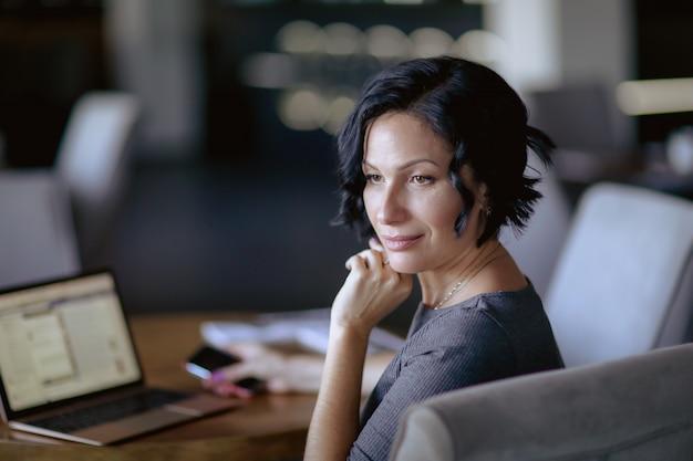 カフェのテーブルに座っていると笑顔の大人の女性ビジネス女性