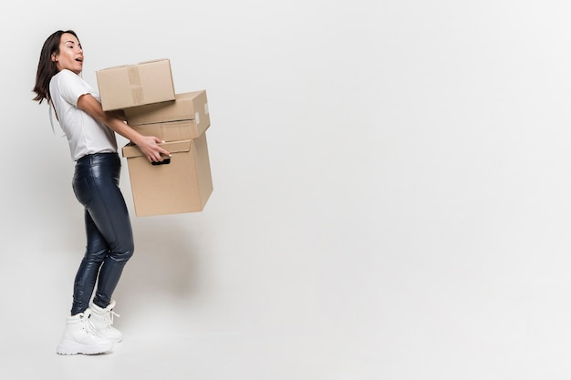 Adult woman carrying cardboard boxes with copy space