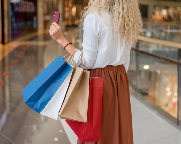 Donna adulta che trasportano le borse della spesa al centro commerciale